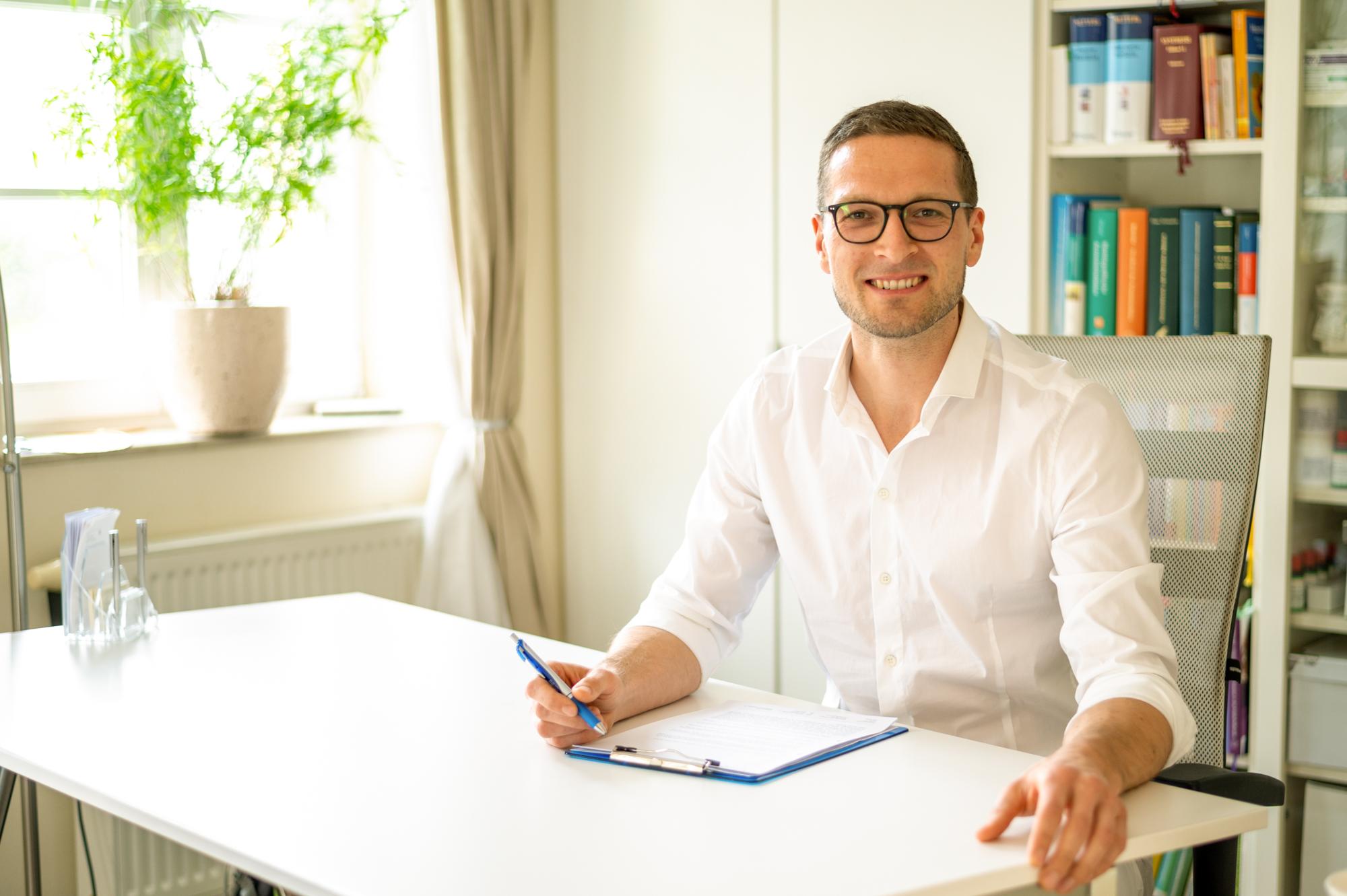 Portrait von Osteopath Richard Müller am Schreibtisch
